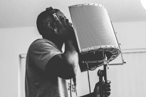 Muscular black man recording his voice for music in a studio