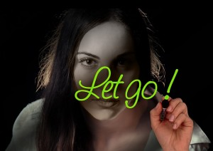"Girl writing ""let go"" on a window while looking into you"