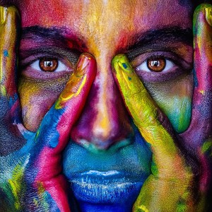 Woman holding face covered in vibrant rainbow of colors