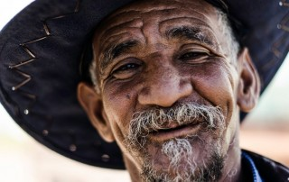 wrinkly smiling man with a cowboy hat on,