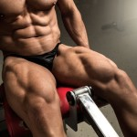 Large muscular man doing leg extensions