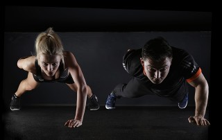 Woman and man doing one-arm pushups on a dark background